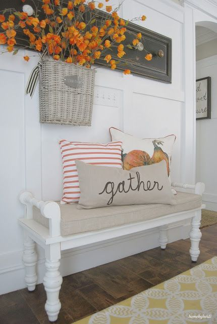 Farmhouse foyer decor - foyer or entryway decorating idea for Fall - Love the white farmhouse bench, the white wood walls and that reclaimed wood / pallet wood wall decor hanger.  The weave basket with dried flowers on the wall is a gorgeous touch that adds a pop of color - and those farmhouse pillows warp it all together.  Easy DIY decor idea for the Fall / Autumn season.